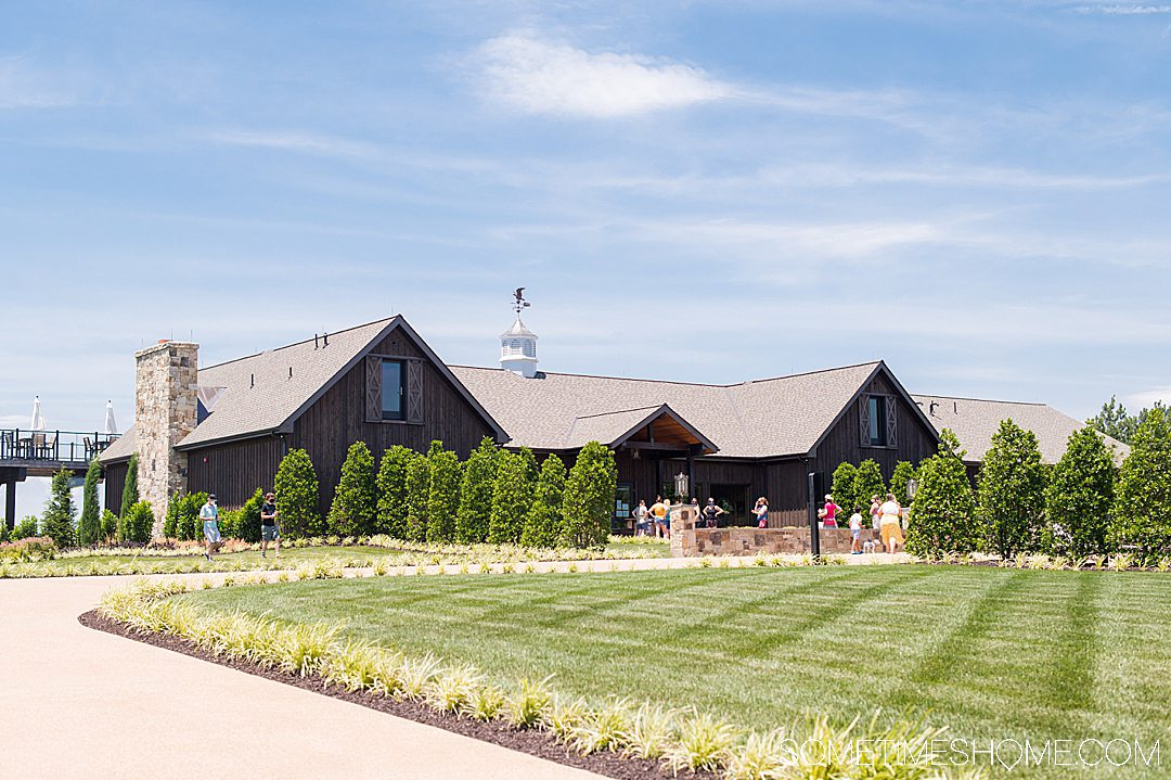 Tasting room photo with a blue sky and green grass.